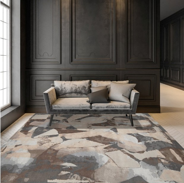 A taupe and grey couch in front of a dark panel wall, with a multicolored earth toned rug
