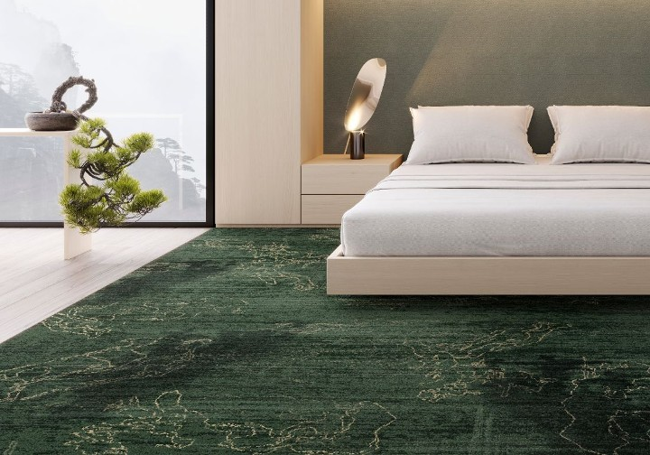 A white bed on an emerald green and gold rug.