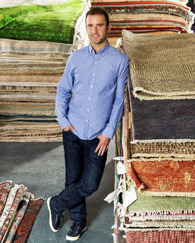 portrait of Noah Krinick leaning against stack of rugs